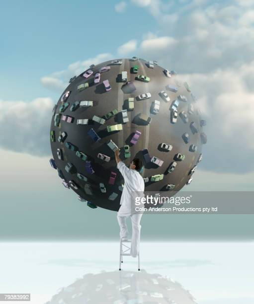 Asian man touching globe covered in cars