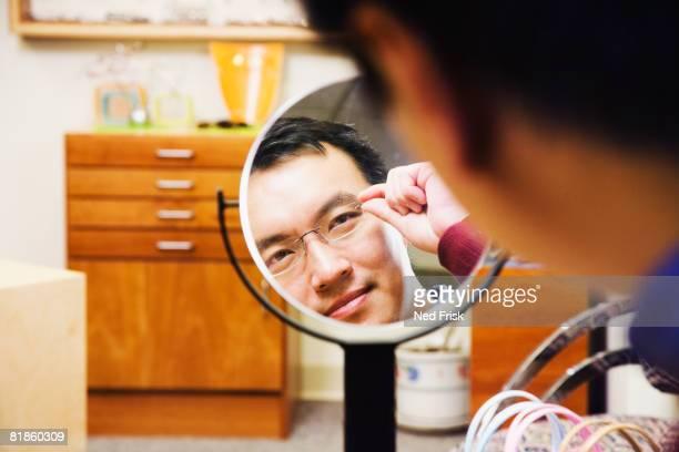 Asian man trying on eyeglasses