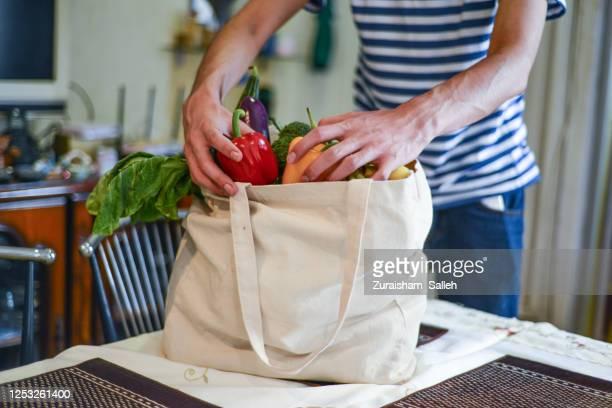 asian man unpacking groceries at kitchen island - comida e bebida imagens e fotografias de stock