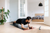 Asian man uses digital tablet to lean plank position