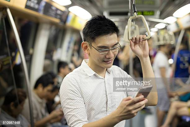 Asian man using a smart phone on underground train.