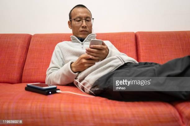 asian man using charging smartphone on sofa - チャージする ストックフォトと画像
