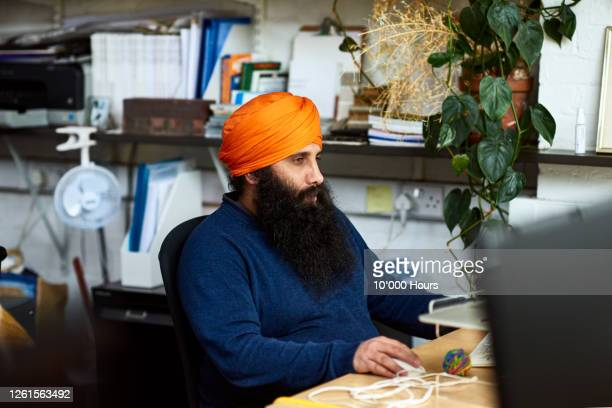 asian man using computer at desk in office - turban stock pictures, royalty-free photos & images
