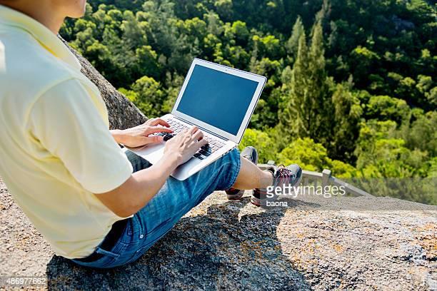Asian man using laptop on rock