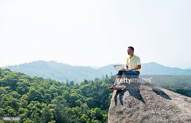 Asian man using laptop on rock