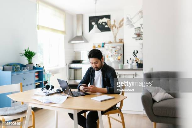 asian man using smart phone while working from home - working from home stock pictures, royalty-free photos & images