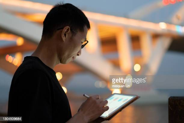 asian man using tablet at night - data stock pictures, royalty-free photos & images