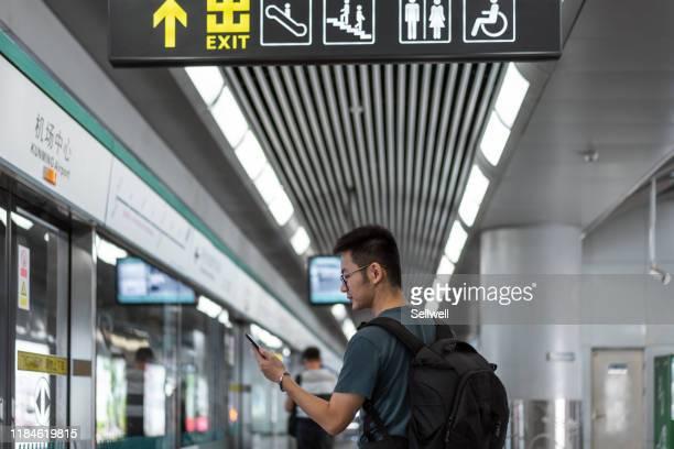 asian man waiting for the train - stazione della metropolitana foto e immagini stock