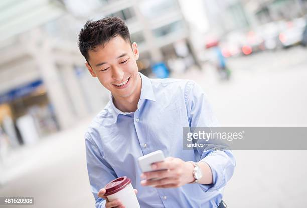 Asian man walking on the street and texting