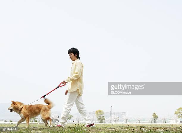 Asian man walking with dog