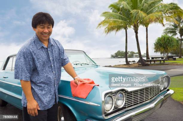 Asian man waxing car