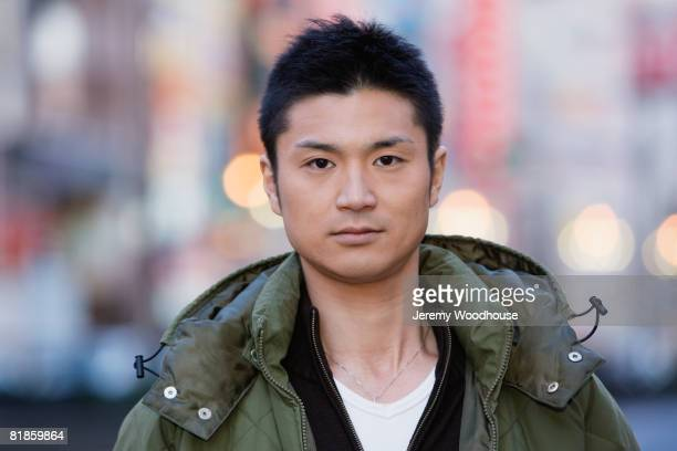 asian man wearing jacket - jeremy woodhouse stock pictures, royalty-free photos & images