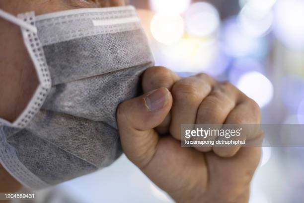 asian man wearing mask and coughing with hand holding on mask - cough foto e immagini stock