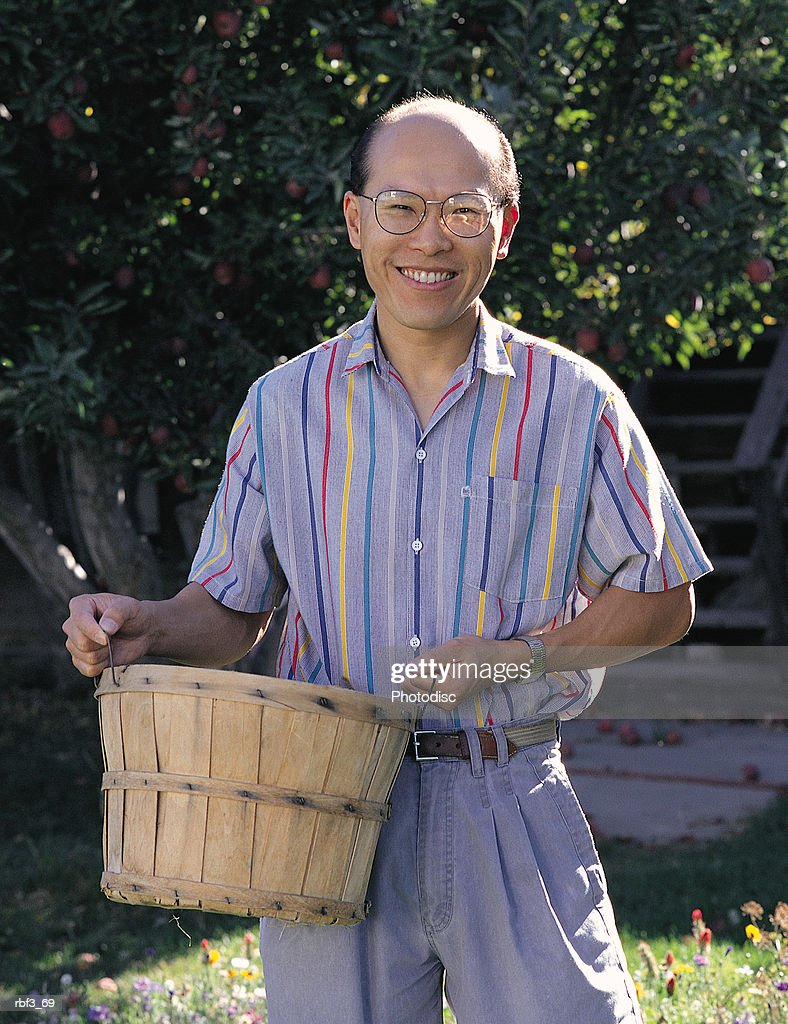 oriental man wears gray pants striped shirt carries a basket smiles standing in a grove of trees : Stockfoto