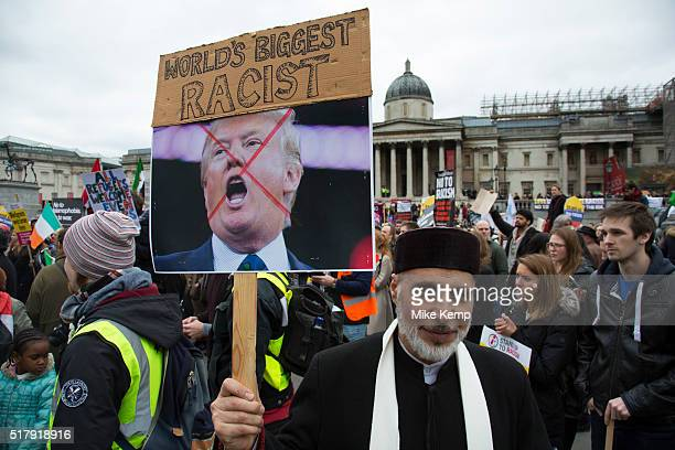 Asian man with a picture of Donald Trump reading World's Biggest Racist amongst demonstrators at Antiracism Day demonstration led by Stand Up To...