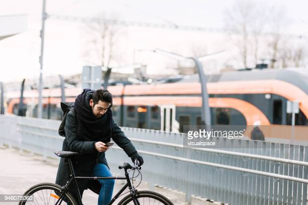 Asian man with bicycle in railroad station using smartphone