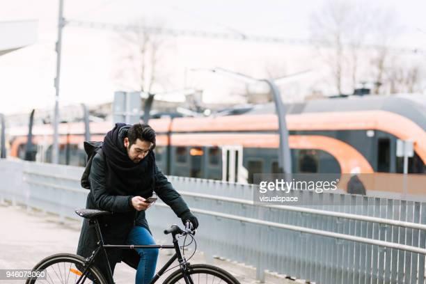 asiatisk man med cykel i railroad station med smartphone - estland bildbanksfoton och bilder