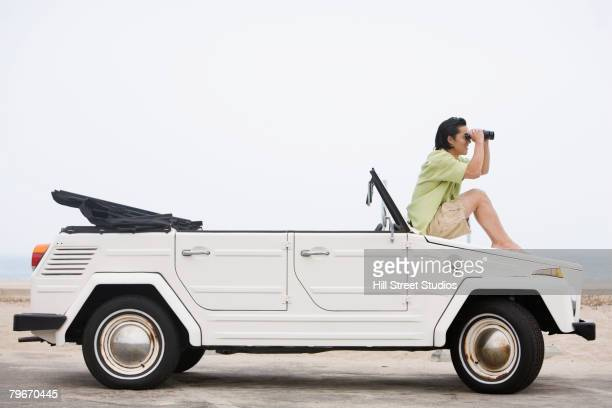 Asian man with binoculars sitting on car hood