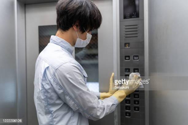 エレベーターのボタンを拭く手袋を持つアジア人男性 - 感染症 ストックフォトと画像
