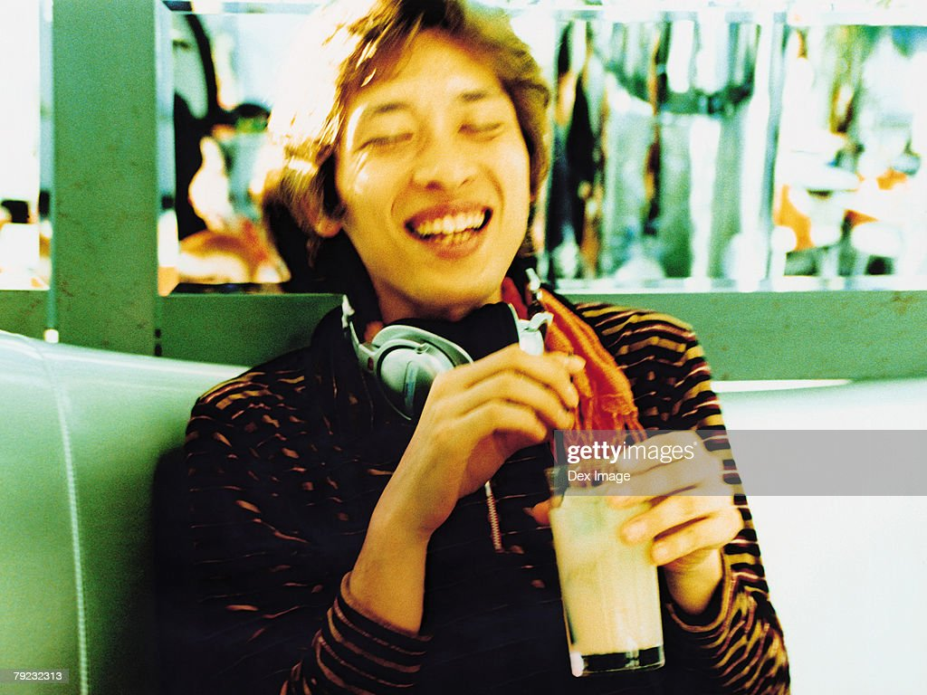 Asian man with Headphones laughing and holding beverage : Stock Photo