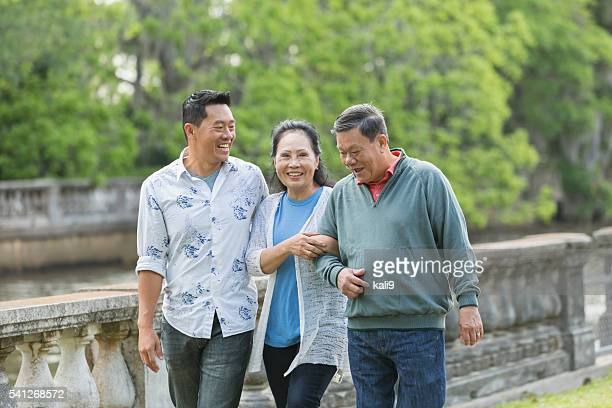Asian man with senior parents in park walking