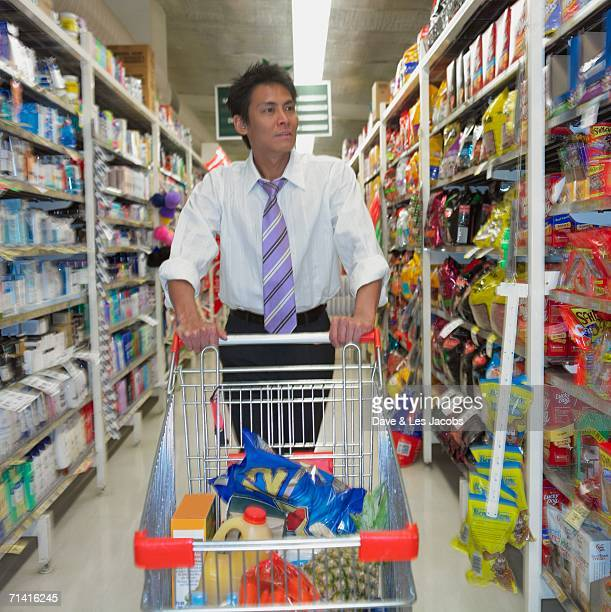 Asian man with shopping cart at supermarket