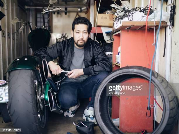 asian man working in a small garage - homens de idade mediana imagens e fotografias de stock