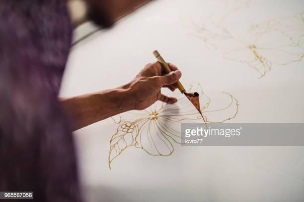 asian man working in batik workshop - batik stock pictures, royalty-free photos & images