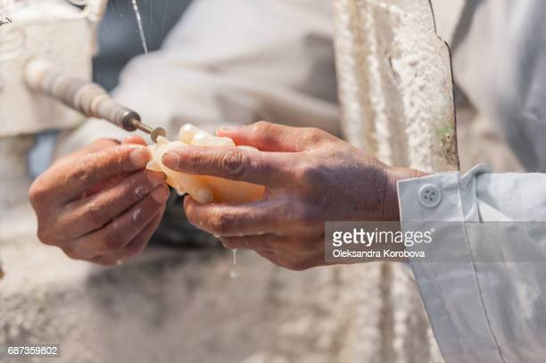 asian man working in the workshop making jade or stone items and figurines - istock photos et images de collection