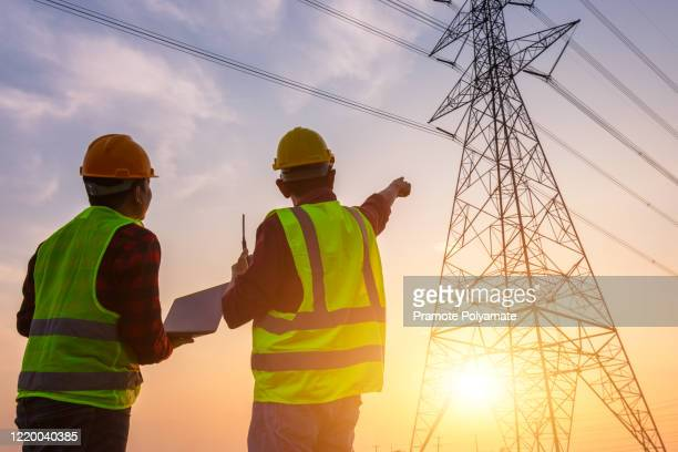 asian manager engineering and worker in standard safety uniform working inspect the electricity high voltage pole. - power occupation stock pictures, royalty-free photos & images