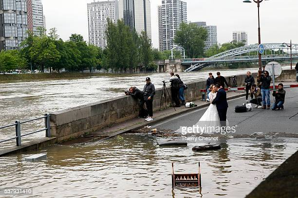 Asian married couple poses in front of the banks of the River Seine became flooded following heavy rainfalls on June 3 2016 in Paris France Northern...