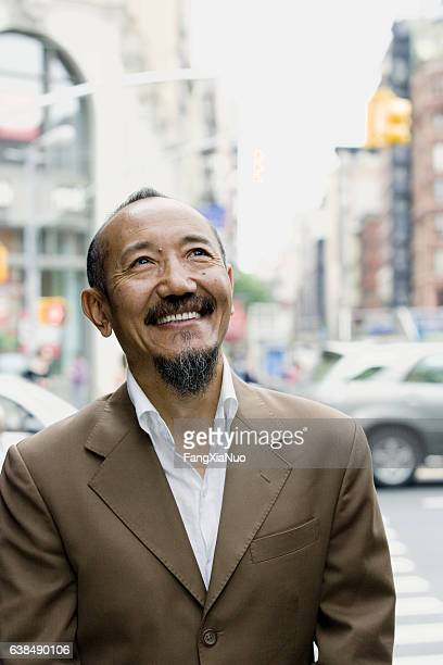 Asian mature man looking upward in downtown city