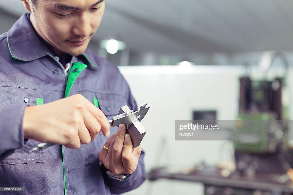 Asian meccanico operaio in fabbrica misurare parti di ricambio : Foto stock