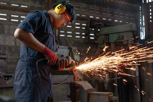 Asian Mechanical engineer operating power tools with metal sparks and copy space 1179565637