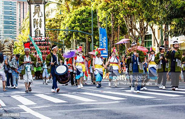 Asian men and women in colorful traditional costume and headwear marching and playing the flute bamboo reed and drums in the annual downtown Pan...