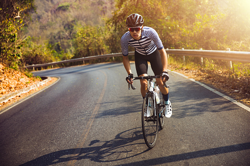 Asian men are cycling road bike in the morning.He is on a forest road. 942488686