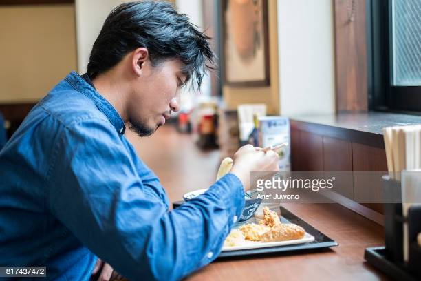 Asian men eat udon