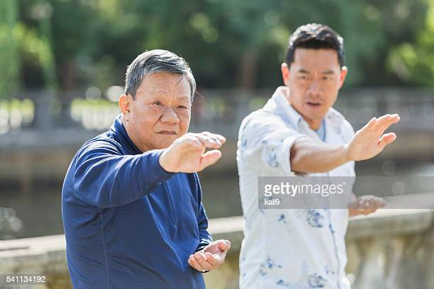 Asian men in park doing tai chi