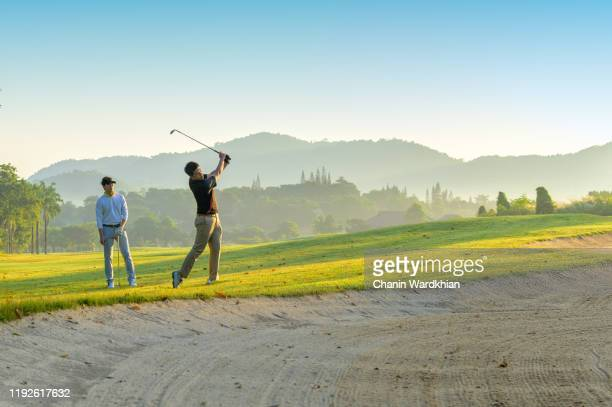 asian men playing golf on golf course - golf stock pictures, royalty-free photos & images