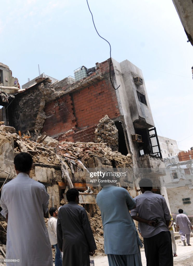 Asian men walk past a destroyed building in the traditional section of the Saudi Red Sea port city of Jeddah on August 17, 2017, following a blaze the previous day which damaged three buildings in the UNESCO world heritage site. Saudi civil defence said 60 people had evacuated their homes when the fire broke late on August 16 in al-Balad, a historic district in the city which dates back to the 8th century. / AFP PHOTO / Amer HILABI