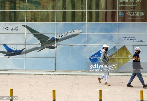 Asian men wearing protective masks walk past a billboard for Kuwait airways in Kuwait City on March 14 2020