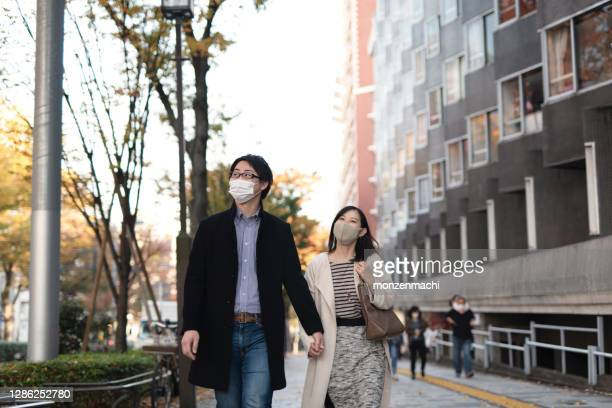 asian mid-adult couple dating in downtown - mid adult couple stock pictures, royalty-free photos & images
