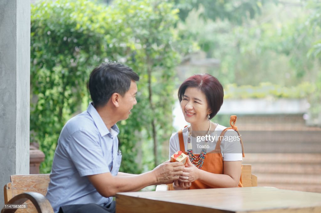 Asian middle-aged man gives a present to his wife in anniversary wedding day : Stock Photo