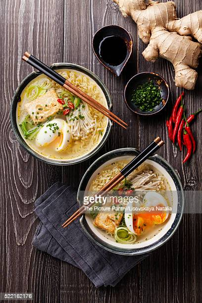 Asian Miso ramen noodles with egg, tofu and enoki in bowls on gr