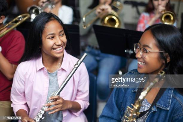 asian mixed race teenage female music students talking and laughing with brass instruments in class - performance group stock pictures, royalty-free photos & images