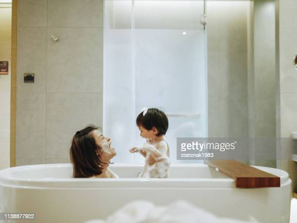 asian mother and baby son having fun at bath time together - boys taking a shower stock pictures, royalty-free photos & images