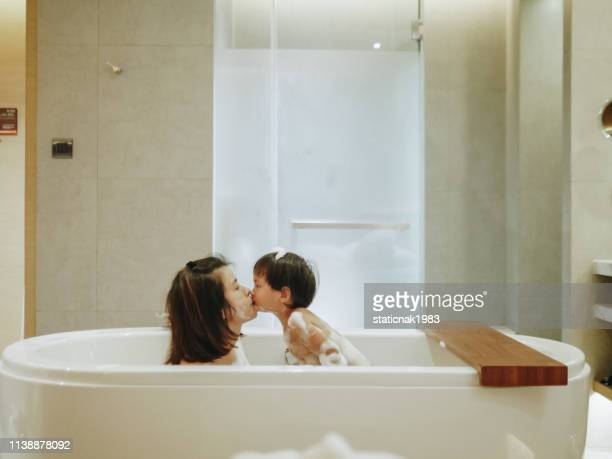 asian mother and baby son having fun at bath time together - mother son shower stock photos and pictures