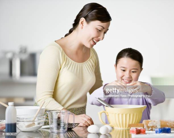 Asian mother and daughter baking cookies
