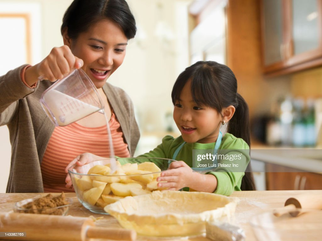 Asian mother and daughter baking pie : Stock Photo