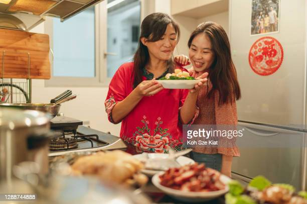 asian mother and daughter bonding during food preparation for chinese new year's eve reunion dinner - chinese new year stock pictures, royalty-free photos & images